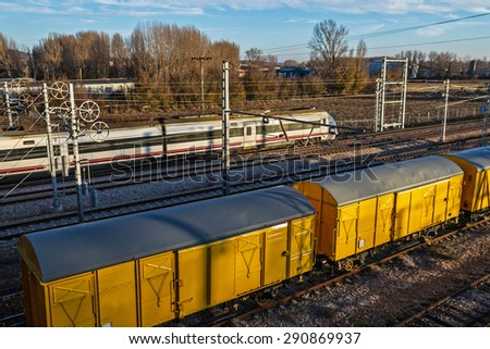 Moving train and train cars freshly painted yellow on the tracks with sunset light - stock photo