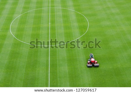 Mowing grass at the football stadium - stock photo