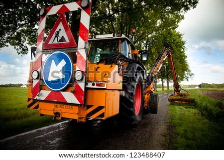 mowing grass shoulder along roadside - stock photo