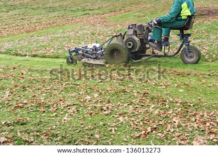 Mowing the grass motor lawn mower in the park - stock photo