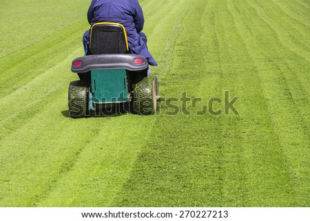 Mowing the grass motor lawn mower on a football field - stock photo