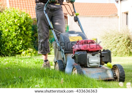mowing the lawn in a garden - stock photo