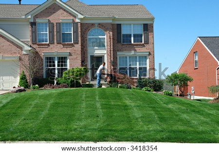 Mowing The Lawn - Professional lawn care company personnel using a riding lawn mower to cut the grass. - stock photo