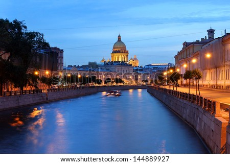 Moyka canal in downtown Saint Petersburg, Russia at twilight with the dome of Saint Isaac Cathedral in the skyline. - stock photo