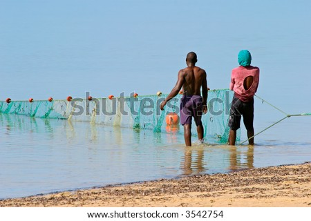 Mozambican fishermen pulling a fishing net from the water - stock photo