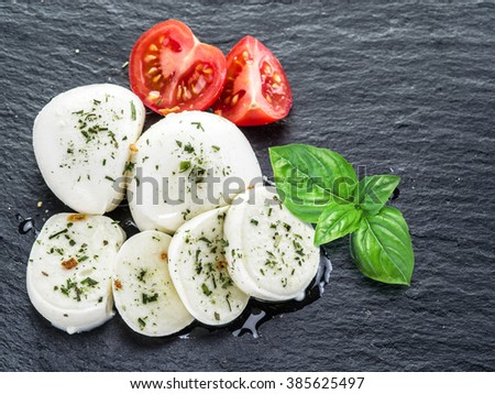 Mozzarella and tomatoes. Dark grey background. - stock photo