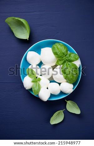 Mozzarella balls with basil, dark blue background, above view - stock photo