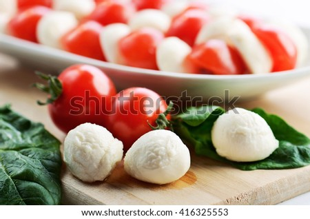 mozzarella cheese balls, ripe cherry tomatoes and caprese salad in a dish on the cutting board. horizontal format - stock photo