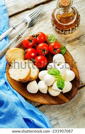 mozzarella cheese on a white wood background. tinting. selective focus on Basil - stock photo