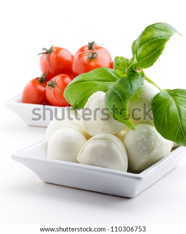 Mozzarella, tomatoes and fresh basil leaves on white background - stock photo