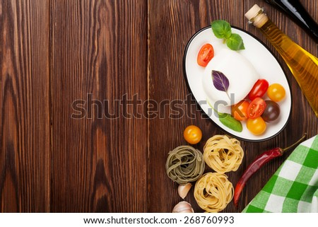 Mozzarella, tomatoes, basil and olive oil on wooden table. Top view with copy space - stock photo