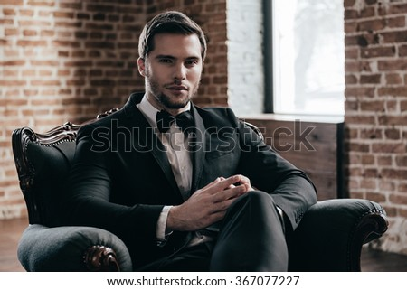 Mr. Confidence. Young handsome man in formalwear and bow tie looking at camera while sitting in a chair in loft interior - stock photo