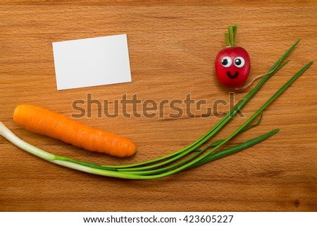Mr. Radish is smiling and looking at the blank card, next are the onion and carrot on wooden table. Close-up view from above - stock photo