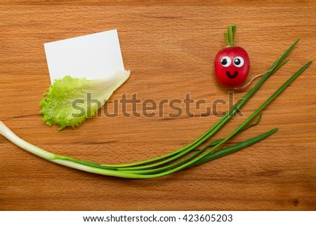 Mr. Radish is smiling and looking at the blank card, next are the onion and lettuce on wooden table. Close-up view from above - stock photo
