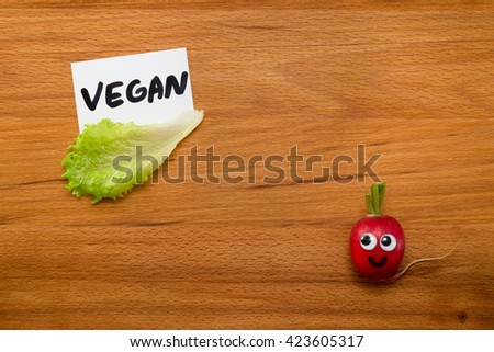 Mr. Radish is smiling and looking at the card with the word 'VEGAN', next are the lettuce on wooden table. Close-up view from above - stock photo