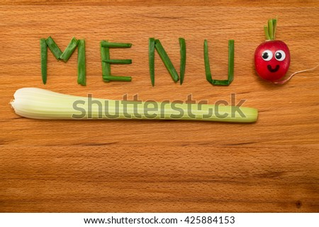 Mr. Radish is smiling and looking at the onion petals folded in the form of the word 'MENU' and celery on wooden table. Close-up view from above - stock photo