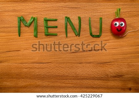 Mr. Radish is smiling and looking at the onion petals folded in the form of the word 'MENU' on wooden table. Close-up view from above - stock photo
