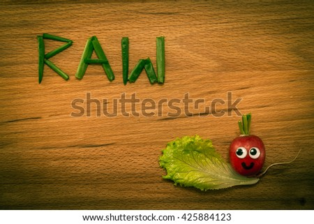 Mr. Radish is smiling and looking at the onion petals folded in the form of the word 'RAW' on wooden table. Close-up view from above, image vignetting and the yellow-green toning - stock photo