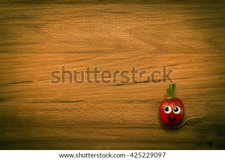 Mr. Radish is smiling on wooden table. Close-up view from above, image vignetting and the yellow-green toning - stock photo