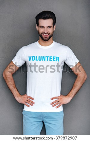 Mr. Volunteer. Confident young man in volunteer t-shirt keeping hands on hips and looking at camera with smile while standing against grey background - stock photo