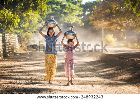 Mrauk-U, MYANMAR - DEC 15, 2014: happy asian traditional  harvest at myanmar, Mrauk-U carrying pots back home at Mrauk-U on December 15, 2014 in Mrauk-U, Myanmar. - stock photo