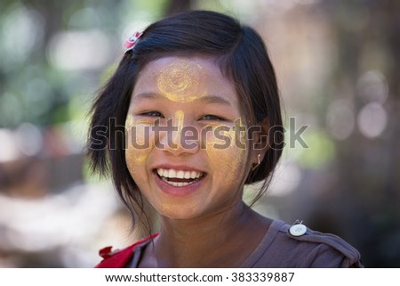 MRAUK-U, MYANMAR - JANUARY 27, 2016: Unidentified young Myanmar girl with thanaka on her smile face is happiness. Thanaka is a yellowish-white cosmetic paste made from ground bark. - stock photo