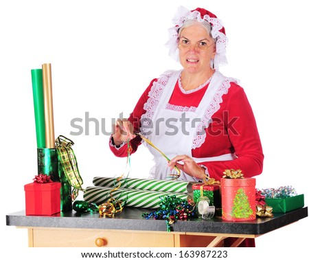 Mrs. Claus trying to decide which ribbon to put use with which wrapping paper as she wraps Christmas gifts.  On a white background. - stock photo