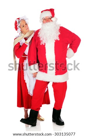 Mrs. Santa inspecting her husband before he takes off on his midnight flight.  On a white background. - stock photo