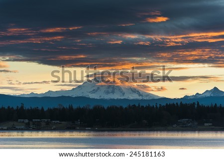 Mt. Baker Sunrise. A very dramatic sunrise paints Mt. Baker with a lovely warm hue. Taken from Lummi Island in the San Juan Islands of Puget Sound in western Washington State. - stock photo