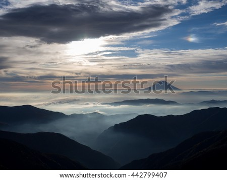 Mt. Fuji over the mist with the overcast sky after sunrise in the morning, captured from Kitadake, Minami South Alps, Yamanashi Prefecture, Japan - stock photo