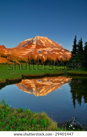 Mt. Rainier seen from Spray Park Meadows reflected in a tarn at sunset - stock photo