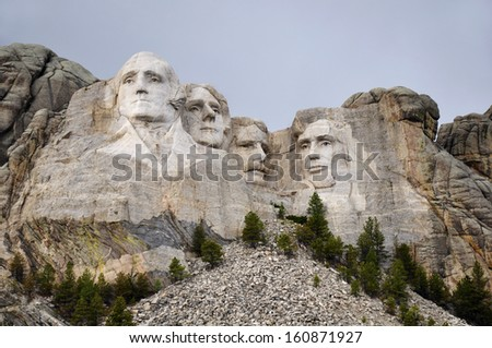 Mt. Rushmore National Memorial Park in South Dakota with neutral sky in background. Sculptures of former U.S. presidents; George Washington,Thomas Jefferson,Theodore Roosevelt and Abraham Lincoln. - stock photo