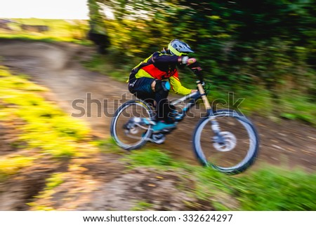 MTB rider in action. speed motion with bluried background, only rider in focus. - stock photo
