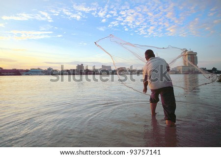 MUAR,MALAYSIA - JAN 1:A fisherman casts his net from the side of Muar estuary river during sunrise on Jan 1 ,2011.Fishing  is still the major economy of some fishing villages in this suburban district - stock photo
