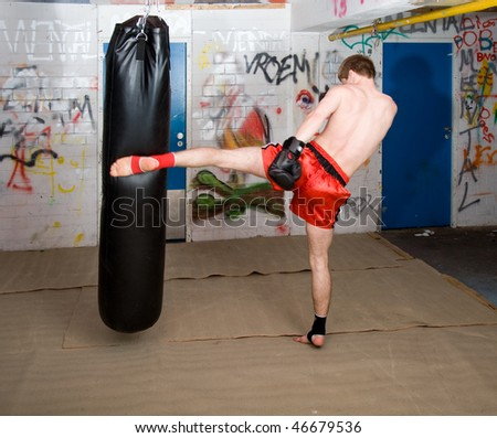 Muay Thai fighter giving a forceful forward kick during a practise round with a boxing bag - stock photo