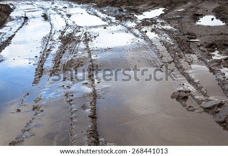 Mud and puddles on the dirt road. - stock photo