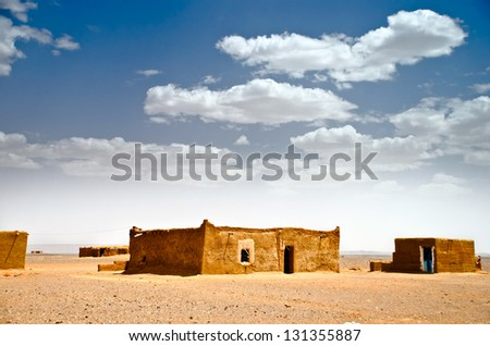mud houses in a desolated landscape, Sahara desert, Morocco - stock photo