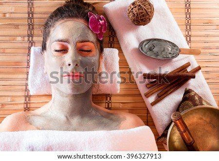 Mud Mask On Face With Cinnamon And Tibetan Singing Bowl  - stock photo