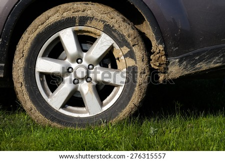 Mud on the wheels at the car on a dirt road - stock photo