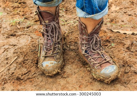 muddy feet-shoes - walking through the mud. - stock photo