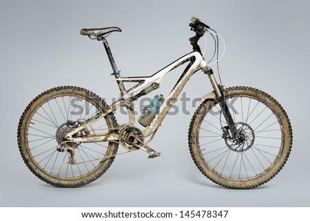 Muddy mountain bike isolated on grey background - stock photo