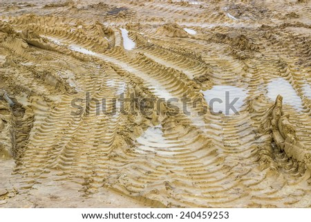 Muddy road with tire tracks and puddles 2. Selective focus. - stock photo