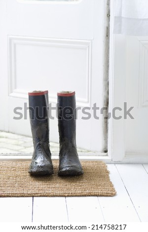 Muddy wellington boots on door mat - stock photo