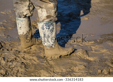 Muddy work boots, human leg with dirty rubber boots. Made with shallow dof. - stock photo