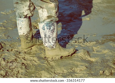 Muddy work boots, human leg with dirty rubber boots. Made with shallow dof and vintage style. - stock photo