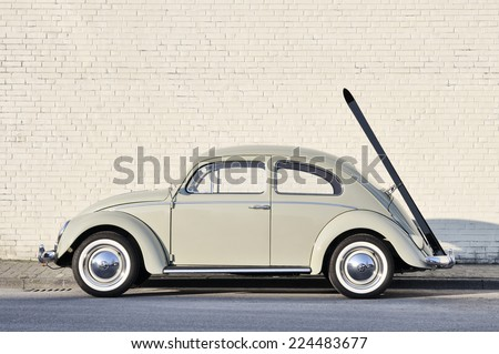 MUENSTER, GERMANY - MARCH 3, 2011: Early 60s VW Beetle, or informally the VW Bug, with ski rack parked in a street. The VW Beetle manufactured and marketed by German automaker VW from 1938 until 2003. - stock photo