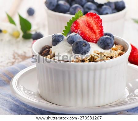 Muesli and yogurt with fresh blueberries. Selective focus - stock photo