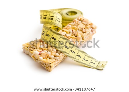 muesli bar and measuring tape on white background - stock photo
