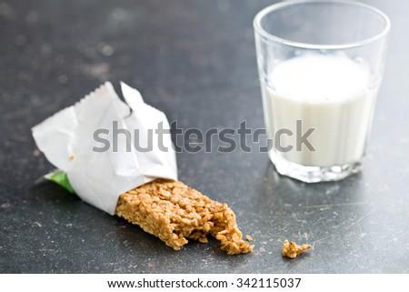 muesli bar and milk on kitchen table - stock photo
