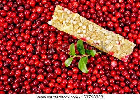 Muesli bar, twig with leaves and berries lingonberry background of lingonberry - stock photo